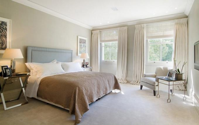 Elongated curtains in the interior of a bedroom